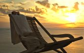 Single chaise lounge with a towel and sunglasses at sunset