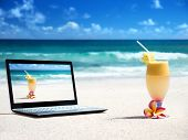 notebook on the beach and glass of fresh juice