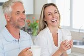Laughing couple having coffee together at home in the kitchen