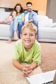 Smiling little boy using laptop on the rug with parents sitting sofa at home in living room