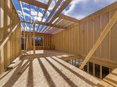 image of 2x4  - New framing house construction with no roof and two by fours exposed - JPG