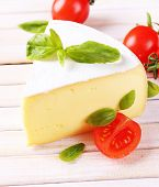 Tasty Camembert cheese with basil and tomatoes, on wooden table