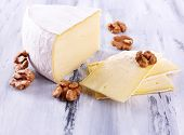 Tasty Camembert cheese with nuts, on wooden table