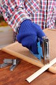 Fastening wooden lath and cork board using construction stapler on bright background