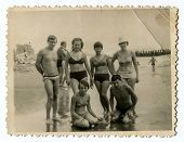 YALTA, USSR - CIRCA 1960s : An antique photo shows group of people wading in the ocean .