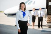 Portrait of confident airhostess with hand on hip standing at airport terminal