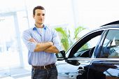 Handsome young man consultant at car salon standing near car