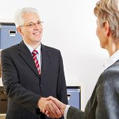 Two elderly business people shaking their hands at a job interview