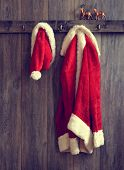 Santa's hat and coat hanging from the coat rack - vintage tone effect