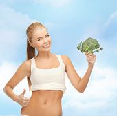 health, diet and food concept - beautiful woman pointing at her abs and holding broccoli