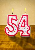 Burning birthday candles number 54 on a wooden background