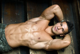 stock photo of hunk  - Attractive muscular young man laying on steps of wooden stair looking at camera shirtless - JPG