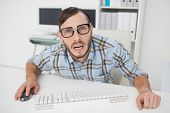 Nerdy stressed businessman working on computer in his office