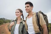 Portrait of hiking young couple standing on mountain terrain