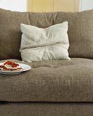 Closeup of toast with jam on plate on sofa