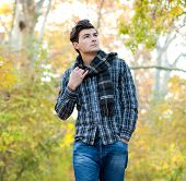 Handsome serious man dressed in a plaid scarf walking in autumn park.