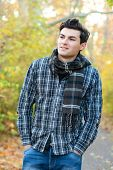 Portrait of the handsome smiling man dressed in a plaid shirt hiking in autumn park.