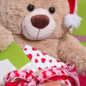 Close Up Of Smiley Teddy Bear With Gift Boxes And Christmas Hat