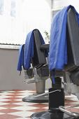 Blue capes on barbers chairs in hair salon