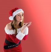 Pretty brunette in santa outfit blowing over hands on red background