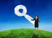 Blindfolded businesswoman with hands out against cloud magnifying glass