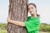 Side view of a female environmental activist hugging tree trunk