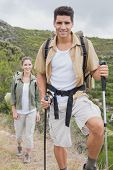Portrait of hiking young couple walking on mountain terrain