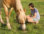 Girl and her horse - horse grazing with girl watching him eat, holding the lead rope