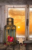 Christmas Background With Red Candle And Lantern - In The Back A Sunset.