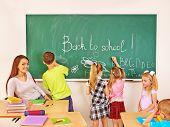 Children writing on blackboard at school.
