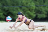 A female beach volleyball athlete on the volleyball court