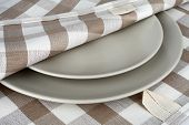 Towel in beige plaid and gray plates. Kitchen towel and plates.