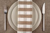 Table setting. Beige plate, fork, knife and beige linen napkin and tablecloth.