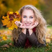 woman lying on autumn leaves, outdoor portrait
