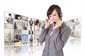 Business woman with headphone standing in front of TV screen wall.