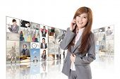 Businesswoman talking on phone and standing in front of TV screen wall.