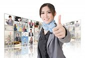 Confident Asian business woman give you a excellent sign standing in front of TV screen wall, closeu
