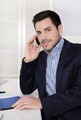 Handsome Businessman Sitting At Desk Talking On Mobile.