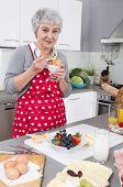 Happy Older Woman Preparing Breakfast And Eating Yogurt.