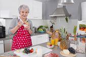 Older Happy Woman Eating Yoghurt In The Morning.