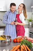 Young Fresh Married Couple In The Kitchen Cooking Together.