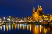 Night City View Of Amsterdam Canal And Basilica Of Saint Nicholas.
