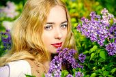 Lovely young woman with magnificent blonde hair near blooming lilac. Countryside.