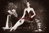 Beautiful ballet dancer posing at studio over vintage background.