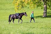 Woman walking with horse on green background outside