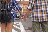 Rear view of a couple  tourists holding hands in a European city.