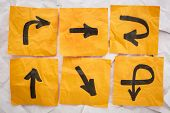 confusing directions concept - a variety of arrows on crumpled, orange sticky notes