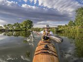 a bow view of a senior male paddling a home-built wooden sea kayak on a lake in Colorado