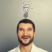 smiley young man looking up at drawing light bulb over grey background