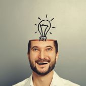 excited smiley businessman looking up at light bulb in the head. photo over grey background